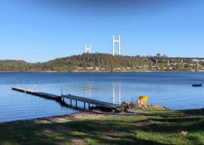 Badplats på campingen med Tjörnbron i bakgrunden.